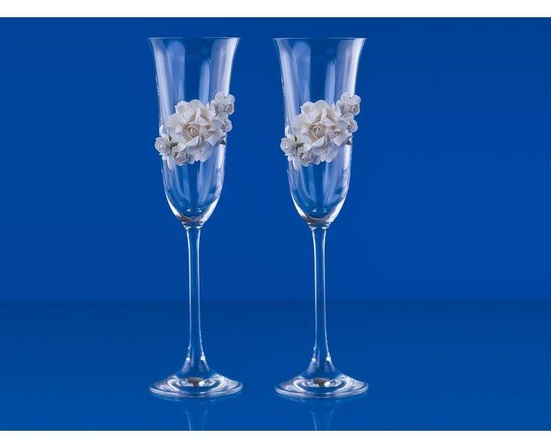 Champagneglazen met een boeket van crème witte roosjes